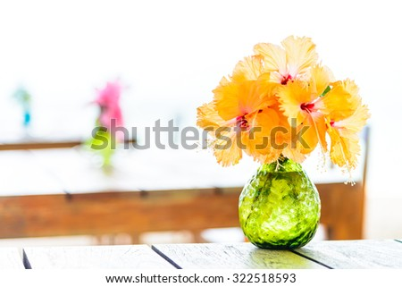 Vase flower on wooden table with sea background