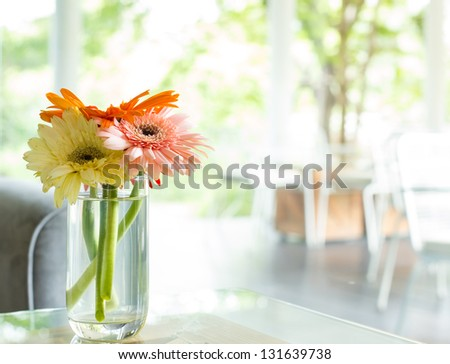 Vase full of  colorful flowers on glass table with sofa at Cafe - stock photo