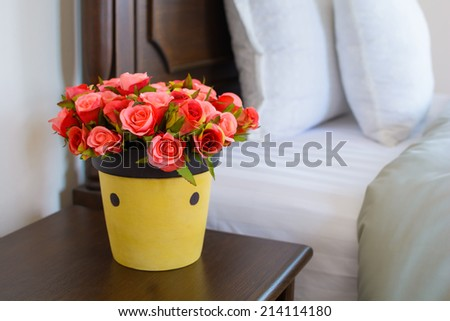 Vase of flowers on a side table near a bed. - stock photo