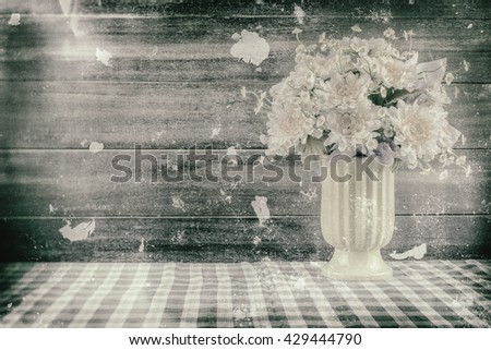 Vase of flowers with a wooden background./ Customize them the picture retro./ Create noise and scratch Simulator./ Convert image files into black and white.