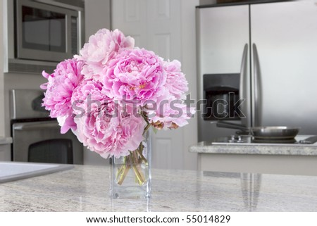 vase of pink peony flowers in modern grey kitchen - stock photo