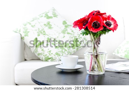 vase of red flowers in modern white living room - home decor with copy space - stock photo
