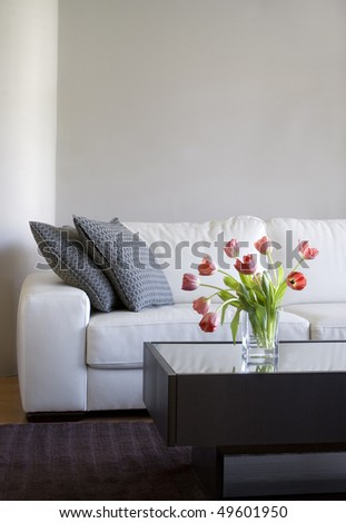 vase of red tulips in modern white living room - home decor - stock photo