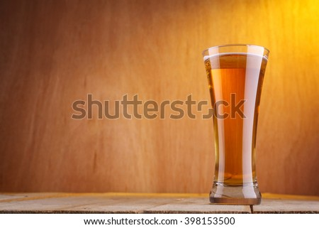 Vase shaped glass with light beer on a grunge wood surface