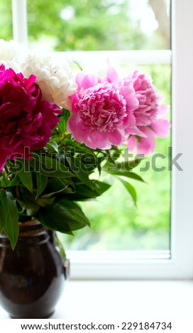 vase with colorful peonies on window-sill - stock photo