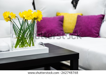 Vase with daffodil flowers in front of white sofa with colorful pillows