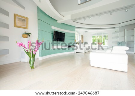 Vase with flowers standing on the parquet in salon