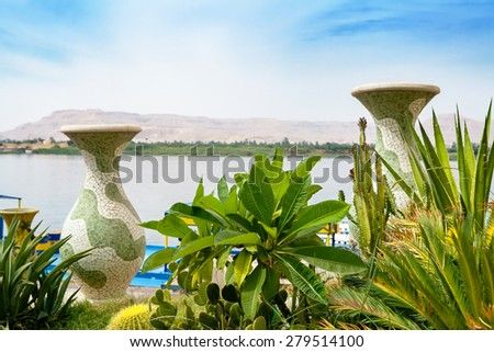 Vases and plants on the banks of the Nile River. Luxor, Egypt, Africa (Background out of focus) - stock photo