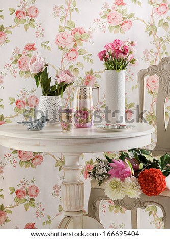 Vases with flowers on a coffee table with floral background  - stock photo