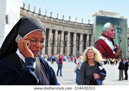 VATICAN - APRIL 28 2011:Black Catholic nun mobile call at St Peter's square Pope John Paul II Vatican city in Rome Italy.Every Sunday at noon the Pope's blessing from his window at St Peter's basilica