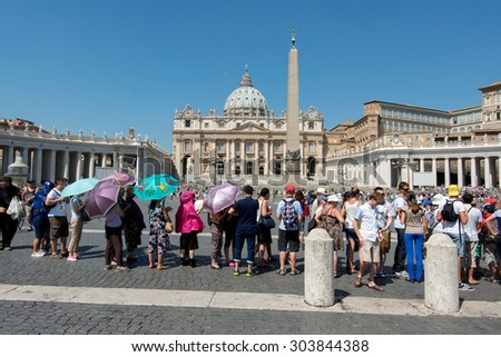 Vatican City - August 06, 2015: Long line of tourists in St. Peter's Square waiting to enter the basilica in the sun of summer in Rome. August 06, 2015