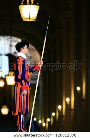 VATICAN CITY, ITALY- APRIL 05: Vatican guard stands in front of Vatican Museum on 5 April 2010 in Vatican, Rome, Italy. The Swiss Guards are responsible for the security of Vatican. - stock photo