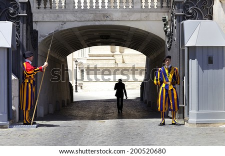 VATICAN CITY, ROME - JUNE 3, 2014: Swiss Guard standing guard with a halberd on June 3, 2014 in Vatican City. Vatican City State is a sovereign city-state within the city of Rome - stock photo