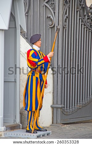 VATICAN CITY, VATICAN - AUGUST 1: Famous Swiss Guard surveil basilica entrance on August 1, 2014 in Vatican. The Papal Guard with 110 men is the world's smallest army. - stock photo