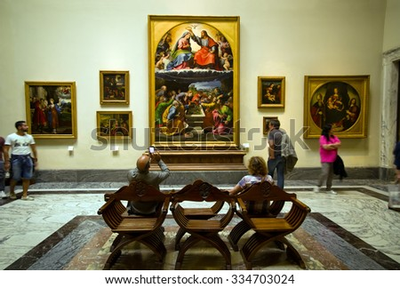 VATICAN CITY, VATICAN STATE - SEPTEMBER 27, 2015: People under the Giulio Romano painting the Coronation of the Virgin aka Madonna of Monteluce 16th-century renaissance classicism, Vatican Museums - stock photo