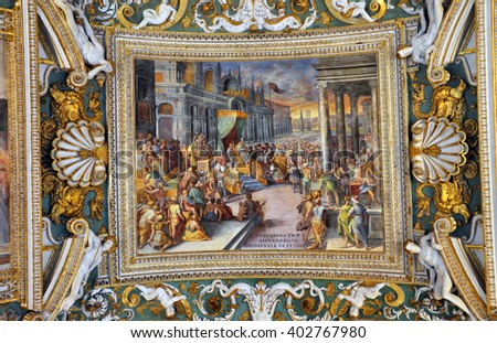 VATICAN, ITALY - MARCH 14, 2016: The carved, ornated and painted ceiling of the Gallery of Maps in the Vatican is visited daily by crowds of people - stock photo