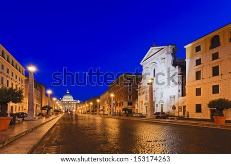 vatican italy rome street cobblestone leading to st peter's cathedral at sunrise illuminated street lamps and ancient houses on sides as landmark