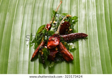 vattal mulaku, Kashmiri/Kashmiry, chili pepper/chile/chilli pepper on banana leaf, genus Capsicum. Dry red chilly pepper, curry leaves used as seasoning  sambar, chutney, curry. Kerala,Tamil Cusines  - stock photo