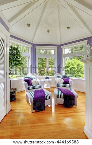 Vaulted ceiling living room in purple tones with two stripped armchairs and hardwood floor.