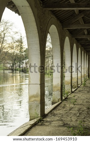 Vaulted old canal side wine wharf in Chablis, France - stock photo
