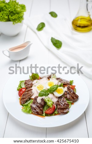 Veal beef fillet medallions warm salad with tomatoes, cucumber, cream sauce, basil and eggs. Restaraunt menu meal in white plate on table background. - stock photo