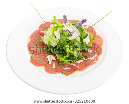 Veal carpaccio with fresh herbs and parmesan. Decorated with flowers. Isolated on a white background. - stock photo