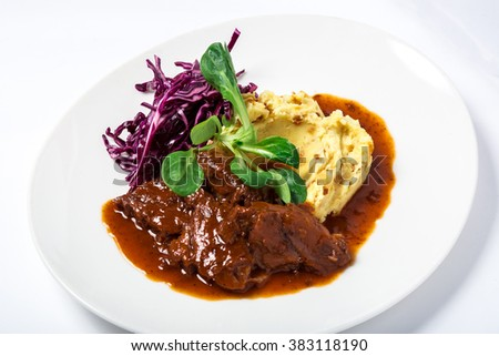 Veal cheeks in gravy with potatoes and cabbage, decorated herbs  - stock photo