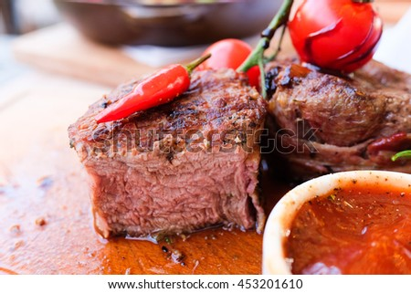 Veal medallions in a cut on a wooden board with a sauce and pepper. Medium Rare, close views horizontal photo