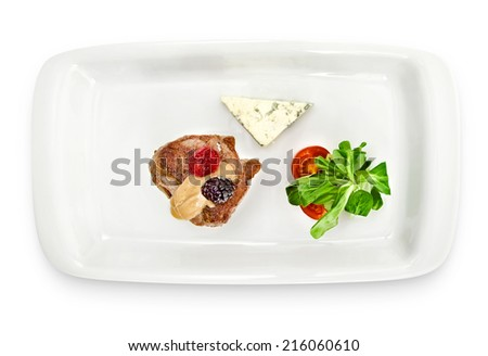 Veal medallions with Dorblu sauce isolated with baked potatoes, cherry tomatoes and light-green mix on white background - stock photo