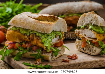 Veal schnitzel - fillet in a bun, with herb mayonnaise, tomato salsa and fresh herbs - stock photo