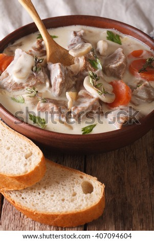 Veal with mushrooms in cream sauce in a bowl on the table. Vertical - stock photo