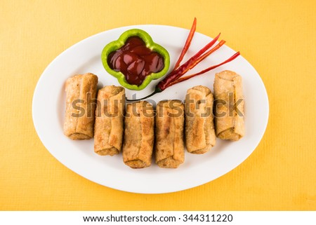 veg roll in white oval ceramic plate with mint leaf, isolated on yellow background, front view