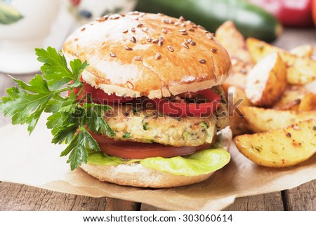Vegan burger with tomato and lettuce, healthy vegetarian version of classic american fast food - stock photo
