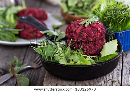 Vegan burgers with beetroot and beans served with fresh vegetables - stock photo