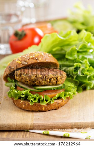 Vegan burgers with lentils and pistachios stacked on a cutting board - stock photo