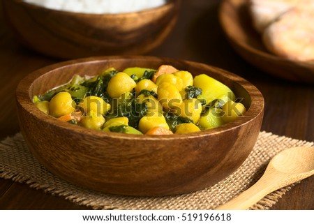 Vegan chickpea curry or chana masala with spinach, potato and carrot served in wooden bowl, photographed with natural light (Selective Focus, Focus one third into the curry)