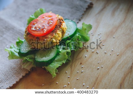 vegan diet Burger appetizer with chickpeas lentil cutlet, cucumber, fresh lettuce, and tomato. Sprinkle with sesame seeds. Sandwich on the wooden table. - stock photo