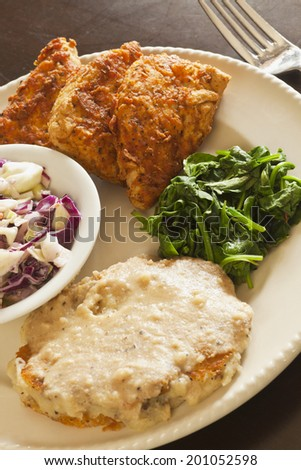 Vegan fried chicken substitute served with slaw, mashed potatoes and greens