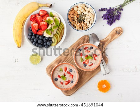 Vegan fruit and berry smoothie breakfast, topped with blueberries, strawberries and mint, seved with fruits, berries and nuts, top view, selective focus - stock photo