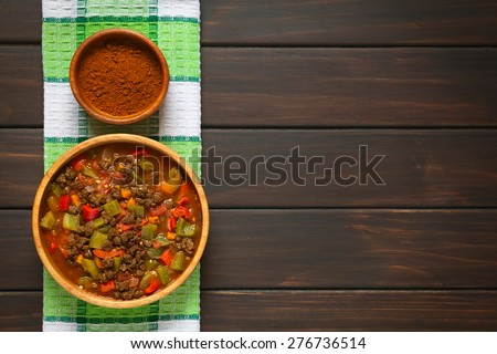 Vegan goulash made of soy meat (textured vegetable protein), capsicum, tomato and onion in wooden bowl, paprika powder in small bowl, photographed overhead on dark wood with natural light - stock photo