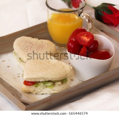 Vegan heart sandwich served in a tray with juice and cherry tomatoes / Healthy valentine Breakfast concept