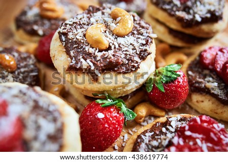 vegan homemade coconut cookies with strawberries and chocolate nut toping, close up