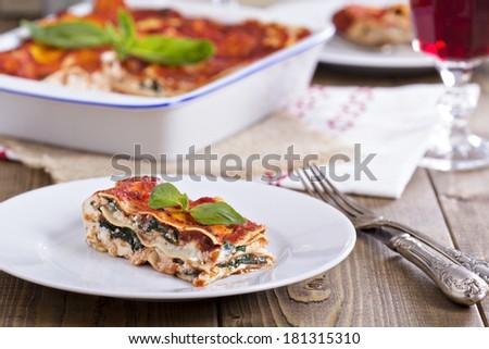Vegan lasagna with tofu, tomato sauce and spinach - stock photo