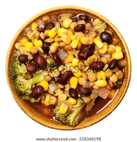 Vegan lentil soup and veggies in bowl with black beans, broccoli, onion, corn over white. Top view. - stock photo