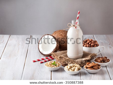 Vegan milk from nuts in the bottle with red stripped straw around various nuts on white wooden table - stock photo