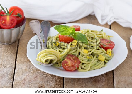 Vegan pasta with avocado sauce, tomatoes and corn