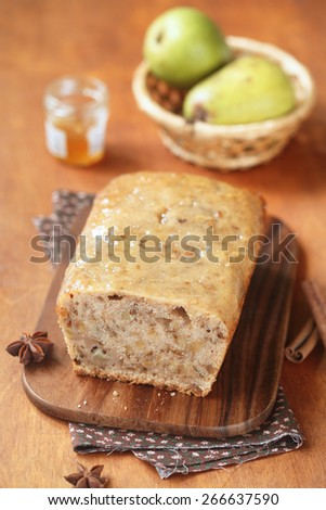 Vegan Pear Walnut Spice Cake on a wooden cutting board, two pears and a little pot of orange jam, on a wooden table. - stock photo