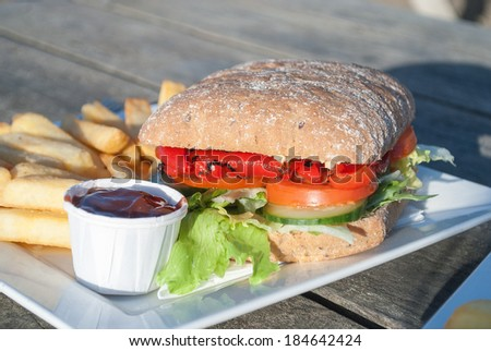Vegan Roasted Pepper and Mixed Salad Sandwich, with chips and tomato sauce.  - stock photo