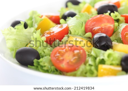 Vegan salad. Ingredients: lettuce, red cherry tomatoes, yellow bell pepper, black olives, olive oil. Shallow depth of field. Close-up. - stock photo