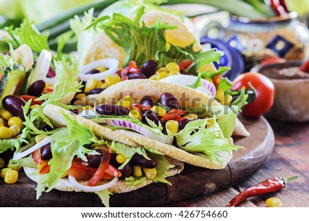 Vegan taco with salad, kidney beans and salsa on a dark wooden board. Selective focus - stock photo